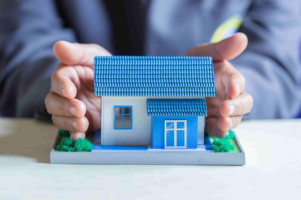 Image d'une maquette de maison étant protégée entre deux mains
