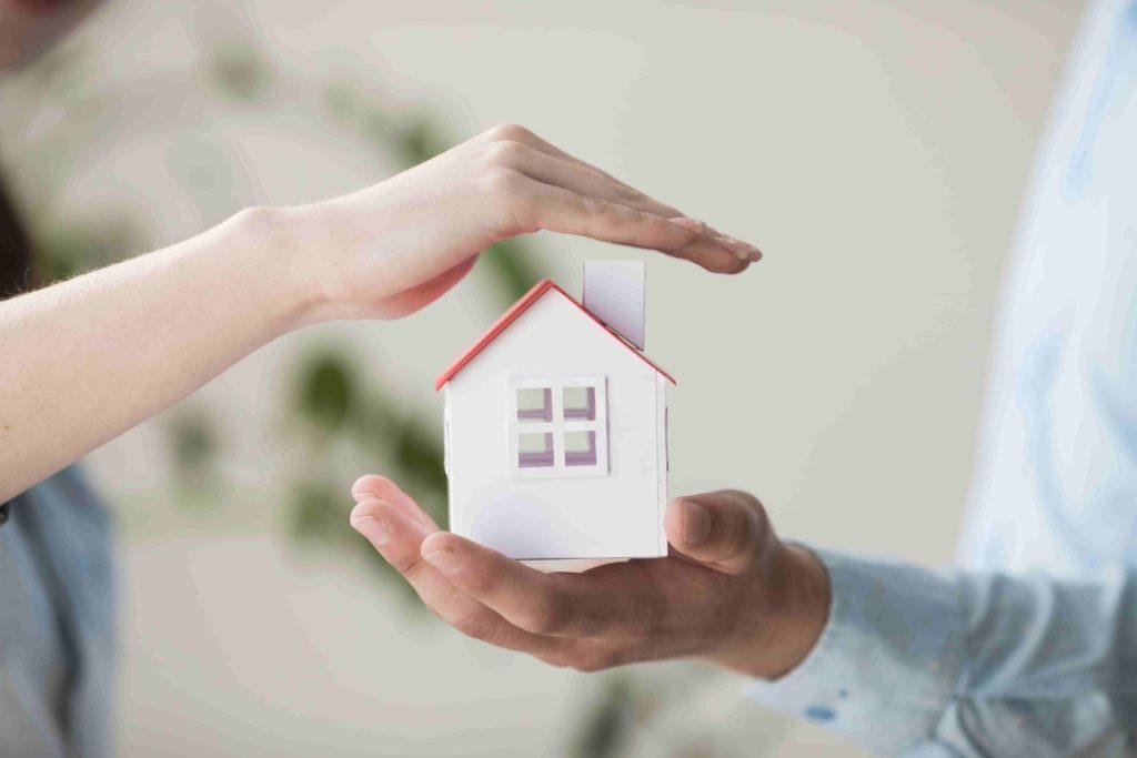 Image de deux mais protégeant une maison en papier - assurance emprunteur