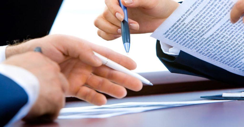 Deux collaborateurs signent un document - Comment constituer son dossier de demande de prêt